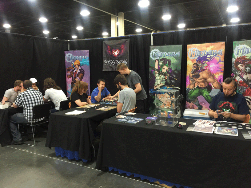 From Left: Our playtest group hard at work, Clayton teaching convention goers how to play, and Brennon cutting out reworked cards for playtesting